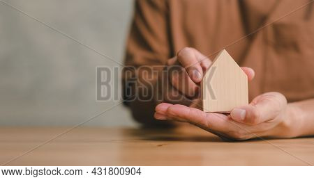 Hands Holding Wooden House Model, Family Home, Homeless Shelter And Real Estate, Housing And Mortgag