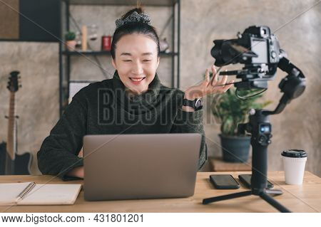 Beautiful Asian Female Sitting At A Desk In A Cozy Living Room And Using Laptop Computer At Home. Sh