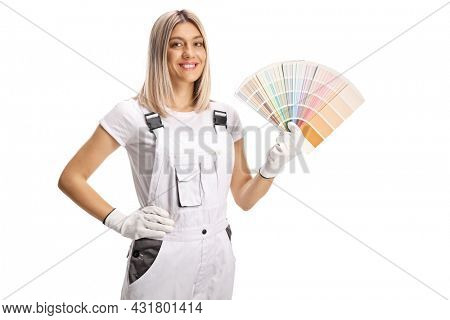 Female house painter in a white uniform holding a color palette and smiling isolated on white background