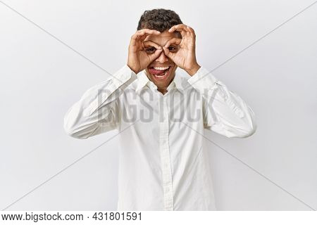 Young handsome hispanic man standing over isolated background doing ok gesture like binoculars sticking tongue out, eyes looking through fingers. crazy expression.