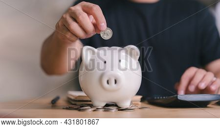 Man Putting Coin On Piggy Bank, Calculate Income And Expenses, Managing Monthly Household Budget Or