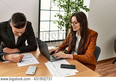 Two hispanic business workers smiling happy working at the office.