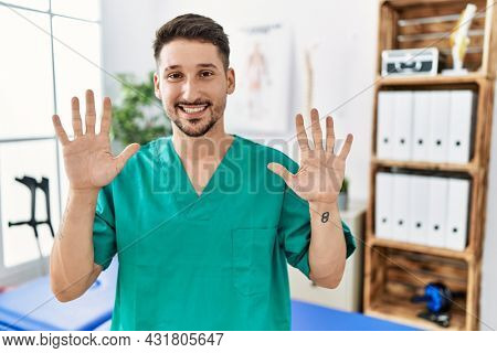 Young physiotherapist man working at pain recovery clinic showing and pointing up with fingers number ten while smiling confident and happy.
