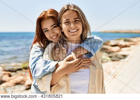 Young lesbian couple of two women in love at the beach. Beautiful women together at the beach in a romantic relationship
