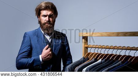 Handsome Bearded Fashion Man In Classical Costume Suit. Male Suits Hanging In A Row. Men Clothing, B