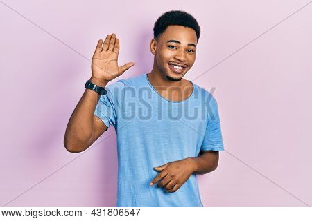 Young african american man wearing casual blue t shirt waiving saying hello happy and smiling, friendly welcome gesture