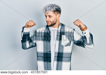 Young hispanic man with modern dyed hair wearing casual shirt showing arms muscles smiling proud. fitness concept.