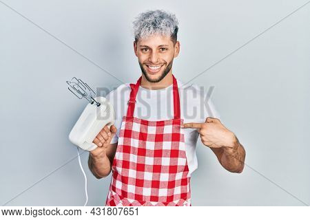 Young hispanic man with modern dyed hair holding food processor mixer machine pointing finger to one self smiling happy and proud