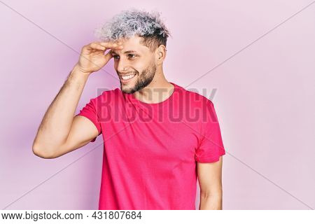 Young hispanic man with modern dyed hair wearing casual pink t shirt very happy and smiling looking far away with hand over head. searching concept.