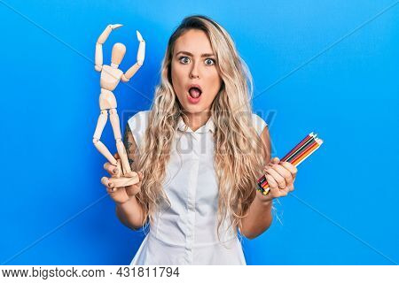 Beautiful young blonde woman holding wooden manikin and colored pencils afraid and shocked with surprise and amazed expression, fear and excited face.