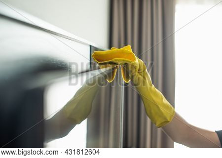 Partial View Of Housekeeper In Rubber Glove Cleaning Tv Display With Rag