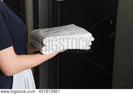 Partial View Of Maid In Uniform Holding Clean Bed Sheets Near Hotel Door