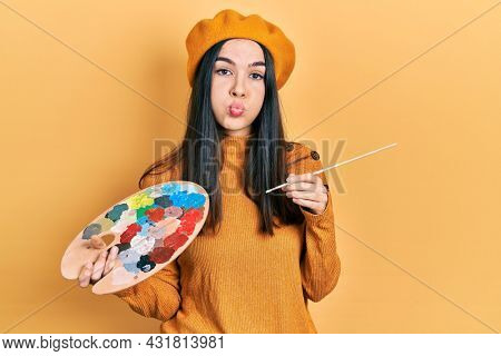 Young brunette woman holding paintbrush and palette wearing beret puffing cheeks with funny face. mouth inflated with air, catching air.