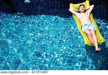 Teenage boy relaxing with pool mattress