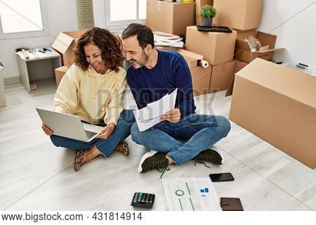 Middle age hispanic couple smiling happy controlling family economy. Sitting on the floor at new home.