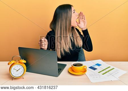 Young hispanic woman working at the office with laptop shouting and screaming loud to side with hand on mouth. communication concept.