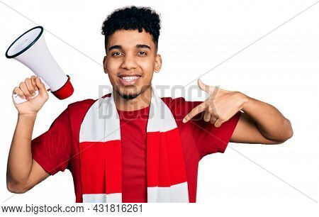 Young african american man football hooligan holding megaphone pointing finger to one self smiling happy and proud