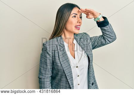Young hispanic woman wearing business clothes very happy and smiling looking far away with hand over head. searching concept.