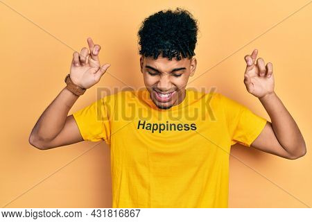Young african american man wearing t shirt with happiness word message gesturing finger crossed smiling with hope and eyes closed. luck and superstitious concept.