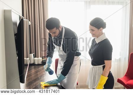 Smiling Maid Looking At Colleague Cleaning Wooden Surface With Rag