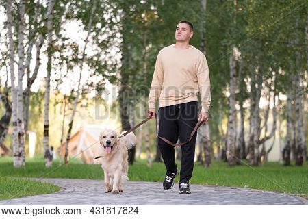 Young Man Walks In The Park With His Dog On A Sunny Day. Golden Retriever Walks On A Leash With Its