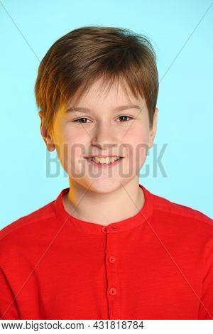 Close-up Portrait: Trendy, Cheerful Teenage Boy In A Red Sweater. He Smiles Broadly And Looks Eye To