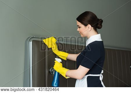 Side View Of Young Maid In Rubber Gloves Holding Spray Bottle And Rag While Cleaning Hotel Room
