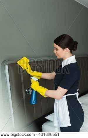Side View Of Young Chambermaid In Rubber Gloves Holding Spray Bottle And Rag While Cleaning Hotel Ro