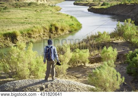 Rear View Of Male Asian Photographer Standing On Top Of A Hill Looking Down At A River