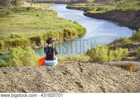 Rear View Of An Asian Woman Sitting On Top Of A Hill Looking Down At Beautiful River Landscape