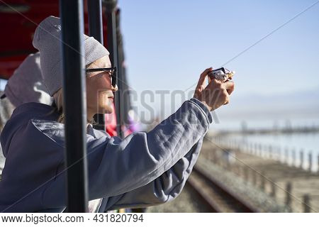 Asian Woman Tourist Taking A Picture Using Cellphone On A Sightseeing Train