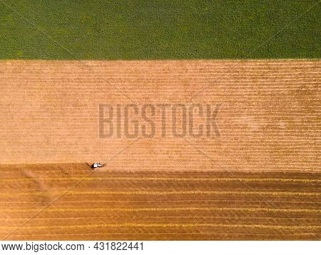 Agricultural Harvester In A Yellow Field Of Wheat. Aerial Drone View Of Colorful Fields. Top Down Vi