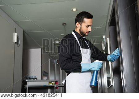 Bearded Housekeeper In Rubber Gloves Cleaning Corridor In Hotel