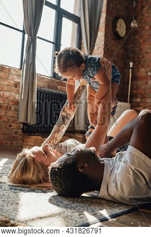 Multi Ethnic Happy Family Of Two Parents And Daughter