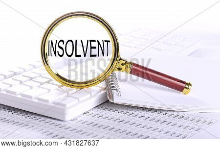 Insolvent Word Through Magnifying Glass On Keyboard On Chart