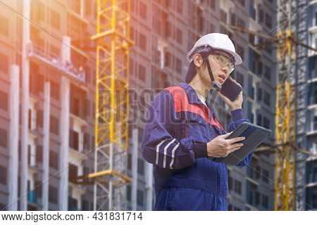 Low Angle View Of Asian Engineer Holding Computer Tablet And Talking On Smartphone While Working In