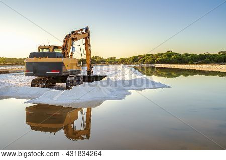 Sea Salt Harvest With Yellow Digger At Salines In Faro, Portugal