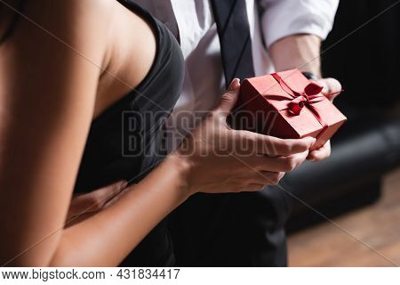 Partial View Of Man Holding Red Gift Box Near Woman In Dress On Black