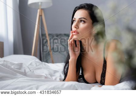 Dreamy Young Woman In Black Bra On Bed