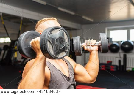 Young Fit Man In A Gym Exercising With Dumbbells.healthy Man Working Out With Dumbbells.copy Space.c