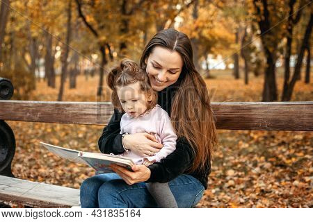 Young Female Woman Babysitter And Toddler Baby Girl Read Book In Autumn Park. Happy Family Mom And T