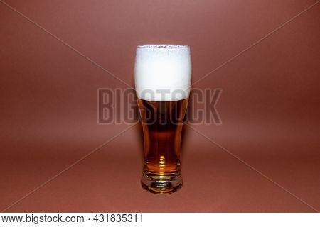 One Glass Beer On Brown Background With Copy Space.amber Glass Beer With Foam.dark Brown Background.