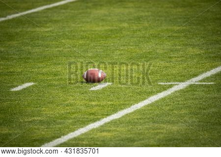 American Football field. Grass field with a football resting on the yard marker. Lots of copy space.