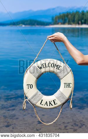 Welcome to the lake. Old lifebuoy on a rope with a beautiful blue Mountain lake in the background. Lake life at the lake house