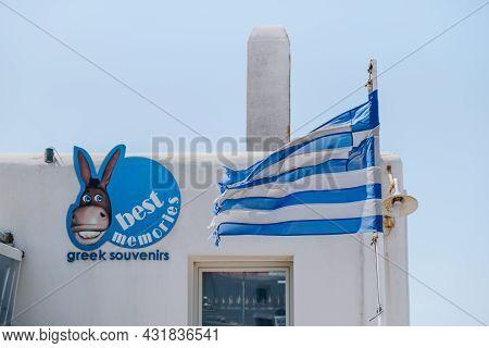 Mykonos Town, Greece - September 24, 2019: Greek Flag Waving In The Wind In Front Of A Souvenir Shop