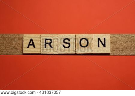 Text The Word Arson From Gray Wooden Small Letters With Black Font On An Red Table