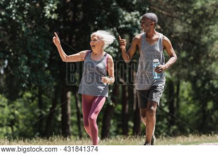 Happy Multiethnic Couple With Sports Bottle Pointing With Fingers While Running In Park.