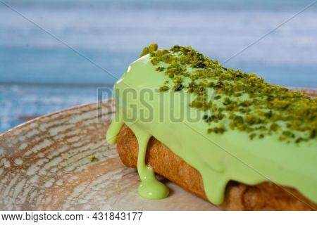 Pistachio Eclair Sprinkled With Green Shavings On A Plate And Blue Background Isolated