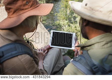 Multiethnic Couple On Blurred Foreground Using Digital Tablet In Forest.