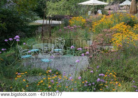 Beautiful Garden With Colorful Wild Flowers. Unkown People In The Distanc. Metal Garden Furniture. S